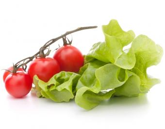 three small tomatoes on a vine with a leaf of lettuce on a white background