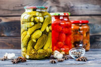 jars of pickled vegetables against a wooden wall