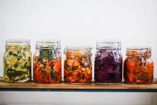 five glass jars with fermented vegetables in them
