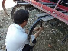Hmong farmer works on farm equipment