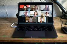 laptop showing a virtual meeting with 8 people's faces