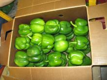cardboard box with green peppers inside of it