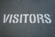 """word """"visitors"""" stenciled on a parking lot"""